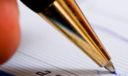 Stylo qui écrit sur une feuille en papier avec des lignes