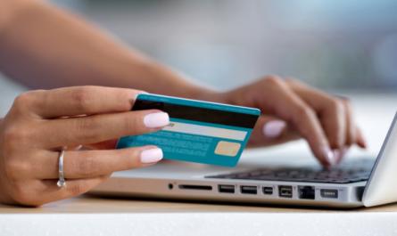 Une femme sur son ordinateur avec sa carte bancaire à la main