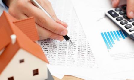 Une maison en papier et des documents sur une table
