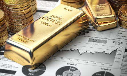 Des lingots d'or posés sur des feuilles de statistiques